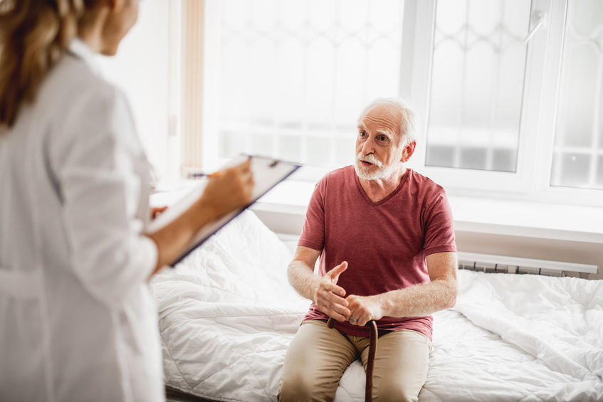 Old man sitting on hospital bed and having conversation with doctor